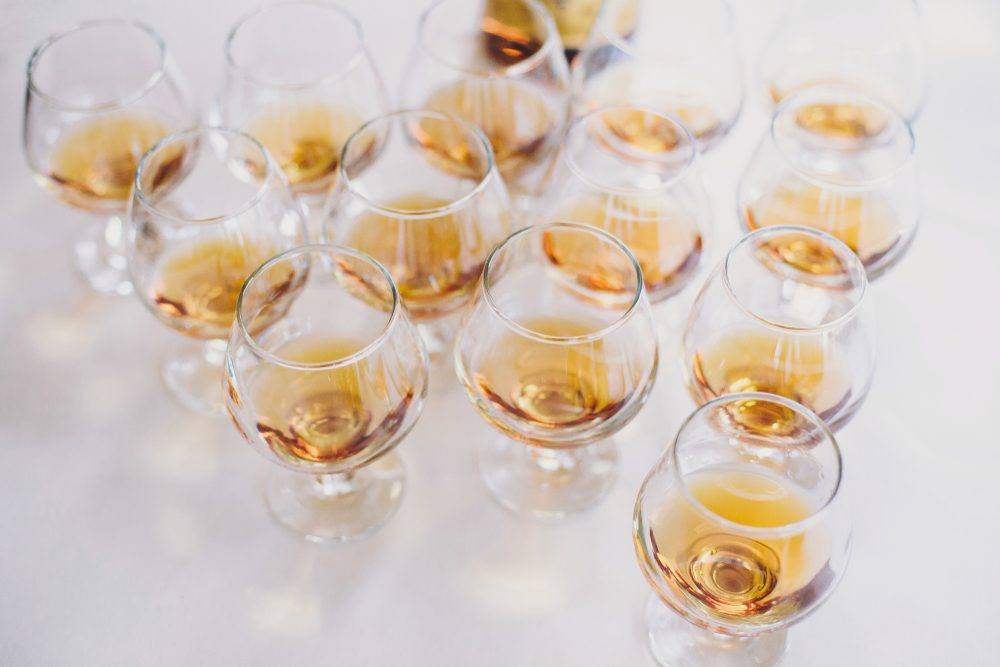 Cognac row on table party at wedding reception. Whisky in glasses at alcohol bar. Christmas and New Year feast. Celebrations and party concept. Alcoholic drinks