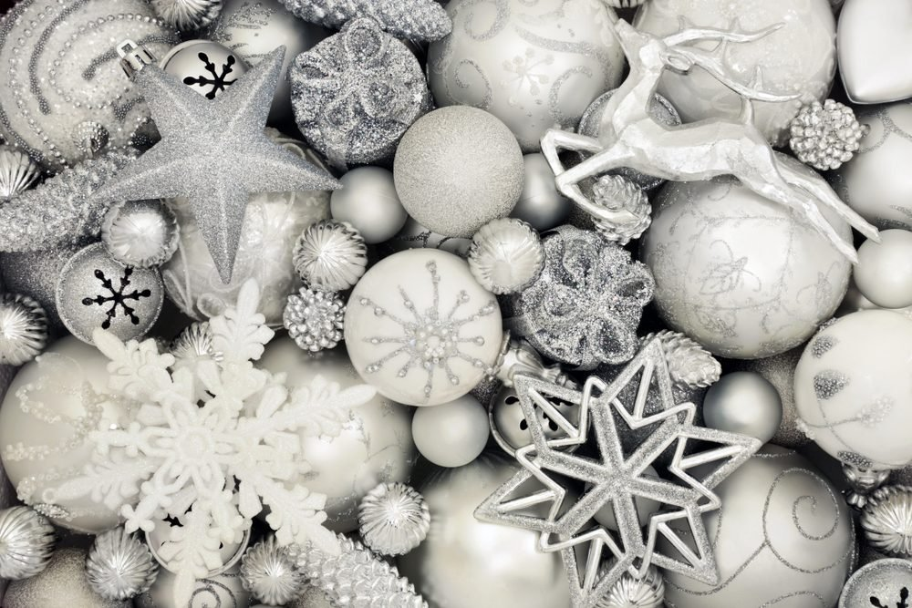 Luxury Christmas silver and white decorations with star, reindeer, snowflake, gift box, balls and pine cone baubles forming an abstract background. Traditional greeting card for the holiday season.