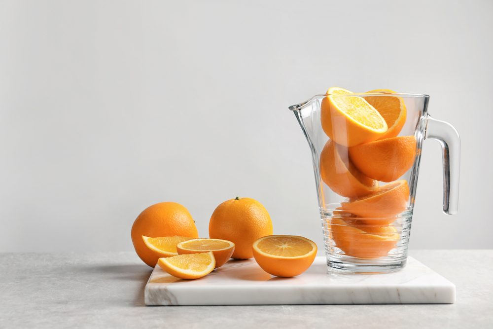 Jug with fresh oranges on marble board. Making juice