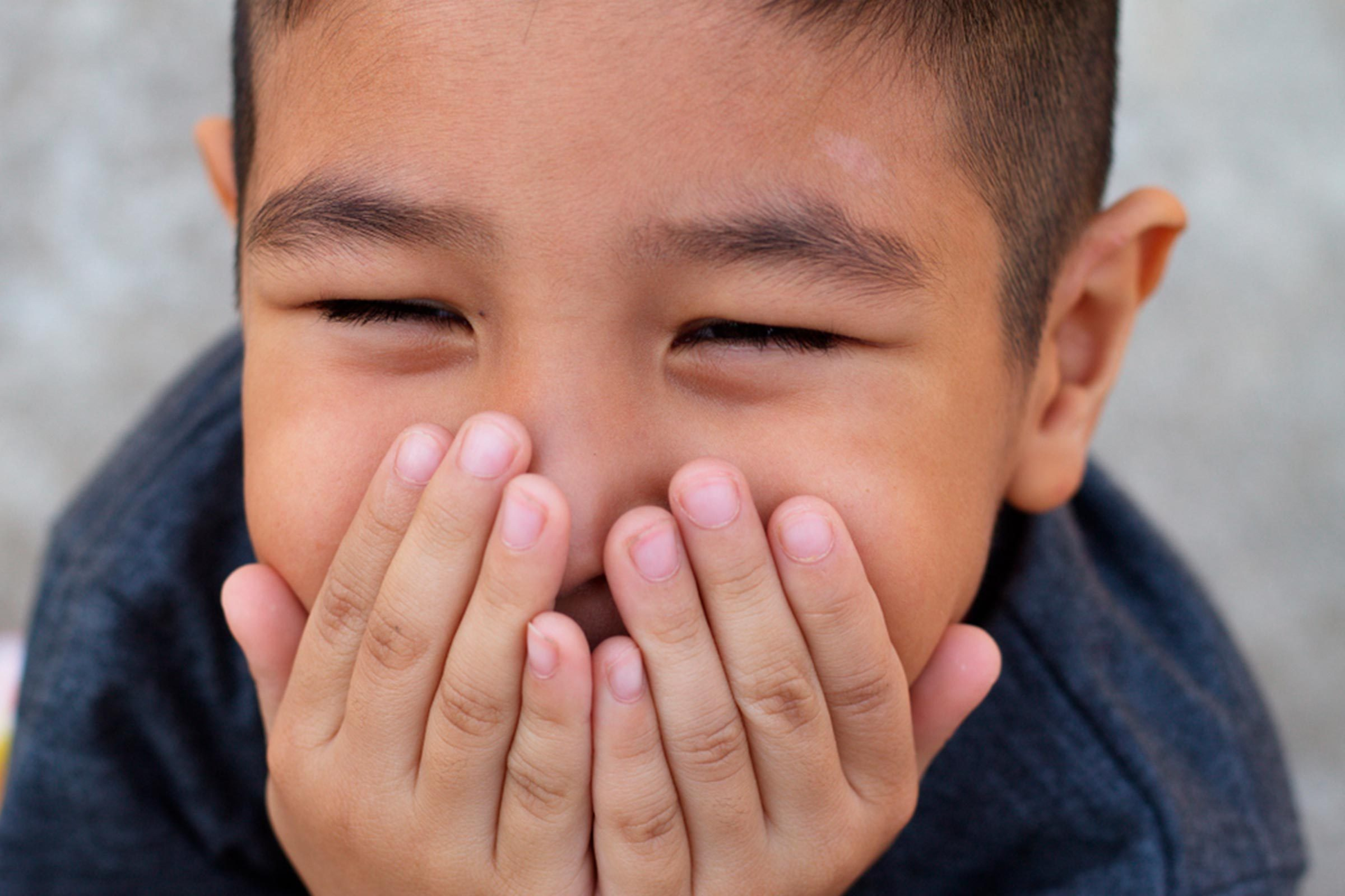Boy covering mouth