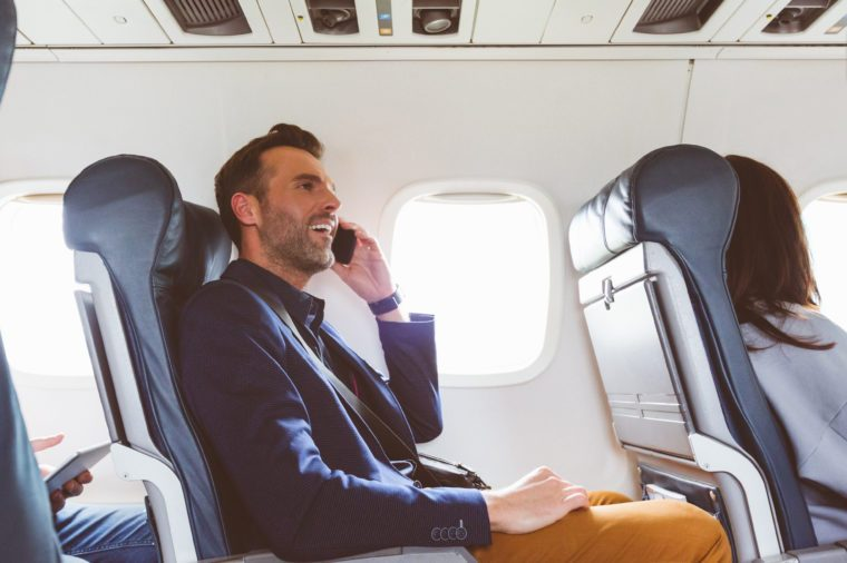 Side view shot of mature man sitting in airplane seat and talking on mobile phone.