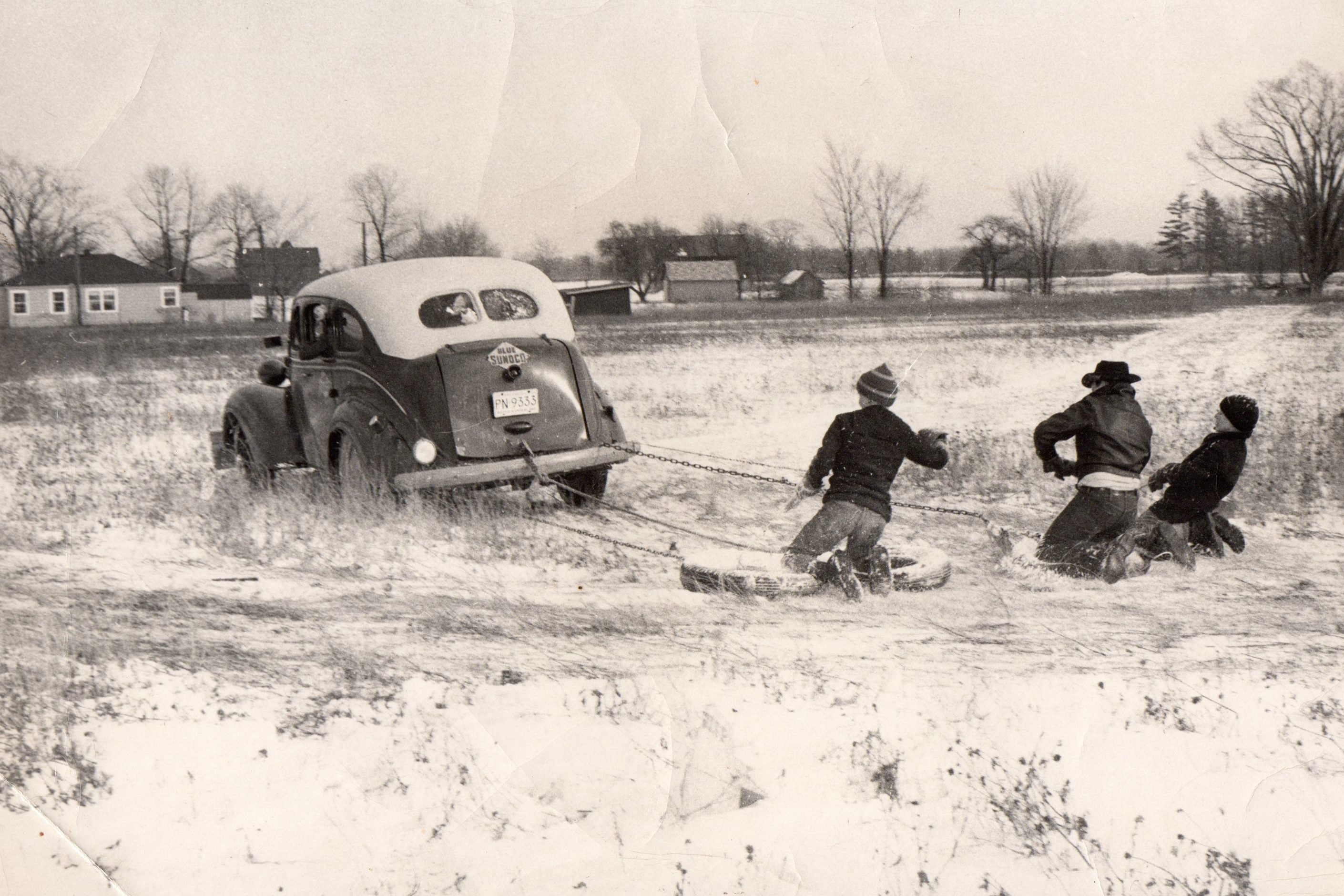 This scene takes place in Goodells; MI. about 1958. The car belonged to my father; Sandy Sanderson. He used the 1937 Dodge with a floor shift as a service car for his gas station (note the large front wooden bumper) to push-start cars. He was inspired to let any of the neighbor kids learn to drive in the field by using his service auto. Most of us learned to drive by 12 to 16 yrs. The object in the winter-the driver was to try to dump anyone riding. When you got cold; places were changed with someone inside the car. The person in the middle was Don Schattler (now deceased) the other two are the Polivich brothers. We drove the car in the field next to my fathers gas station; the tires we rode on; ropes; and chains were furnished by him.