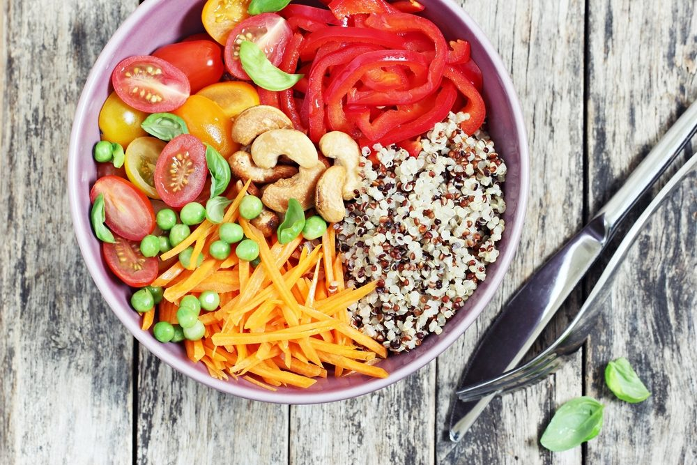 Quinoa bowl with raw vegetables and nuts. Superfoods and clean eating concept. Selective focus