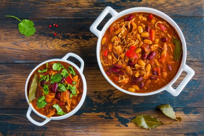 Turkey chili, ,stewed with beans, tomatoes, bell pepper, onion, garlic, thyme, cinnamon, chocolate and fresh cilantro, in white bowl and casserole on wooden table.