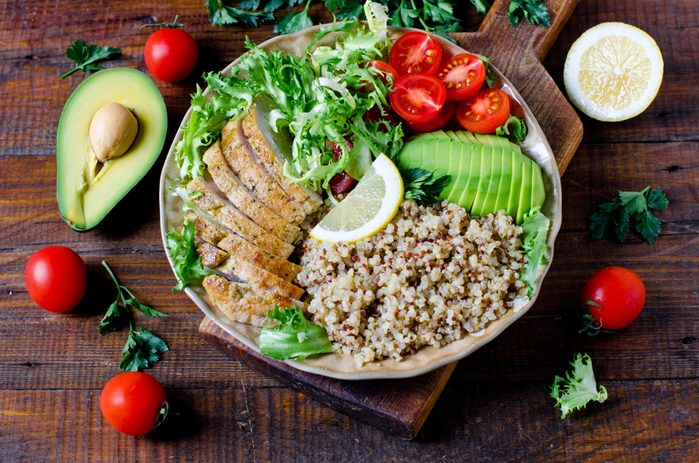 Healthy salad bowl with quinoa, tomatoes, chicken, avocado, lime and mixed greens, lettuce, parsley on wooden background close up. Food and health.