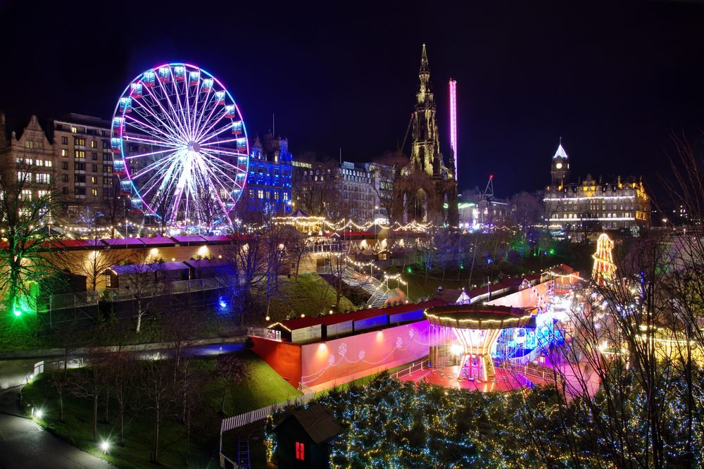 The famous Christmas Market at Edinburgh, Scotland. Night lights lit up setting a lovely scene against the night sky.