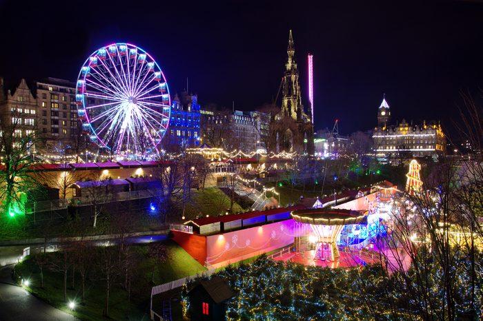 The famous Christmas Market at Edinburgh, Scotland. Night lights lit up setting a lovely scene against the night sky.