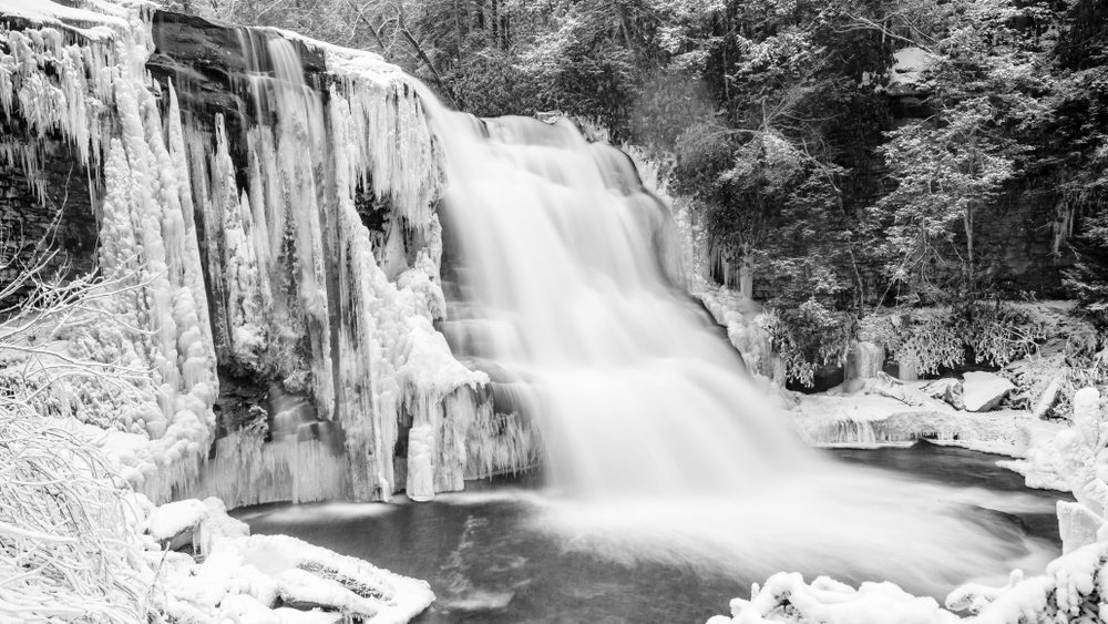 Muddy Creek Falls. The massive water movement of this stunning water fall contrasts with the frozen landscape surrounding it.