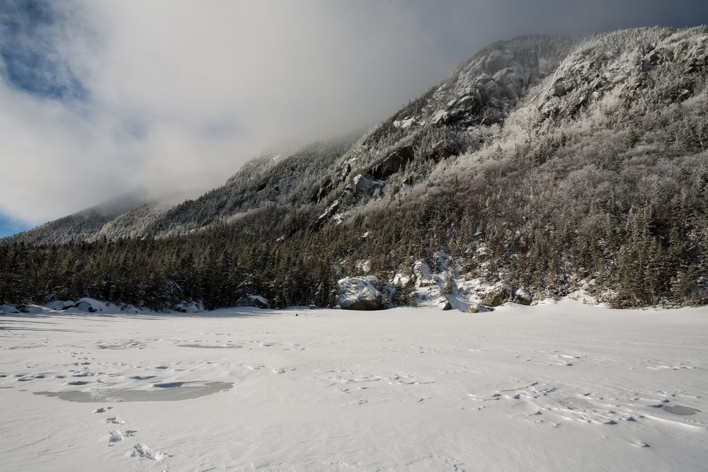 Snow squall over Wildcat Mountain with frozen, snowy pond in foreground, White Mountain National Forest, New Hampshire, USA.