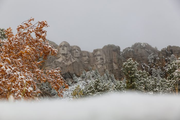 Iconic Mount Rushmore South Dakota showing the Presidents surrounded by snow. Capturing the amazing landscape scenery of the Black Hills coming into winter.