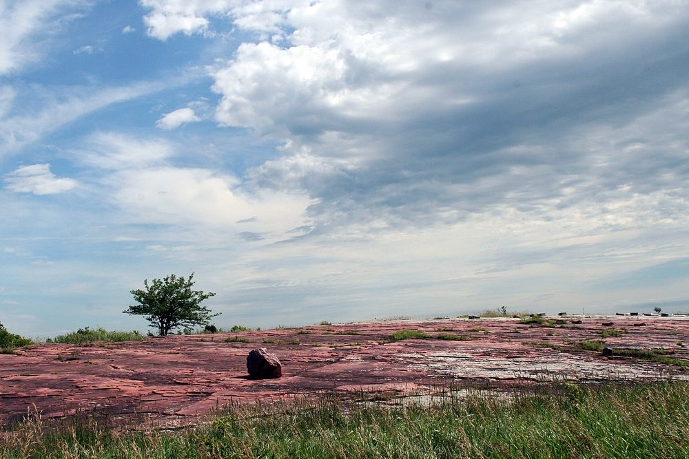 Jeffers Petroglyphs western Minnesota red rocks blue sky clouds and prairie grass