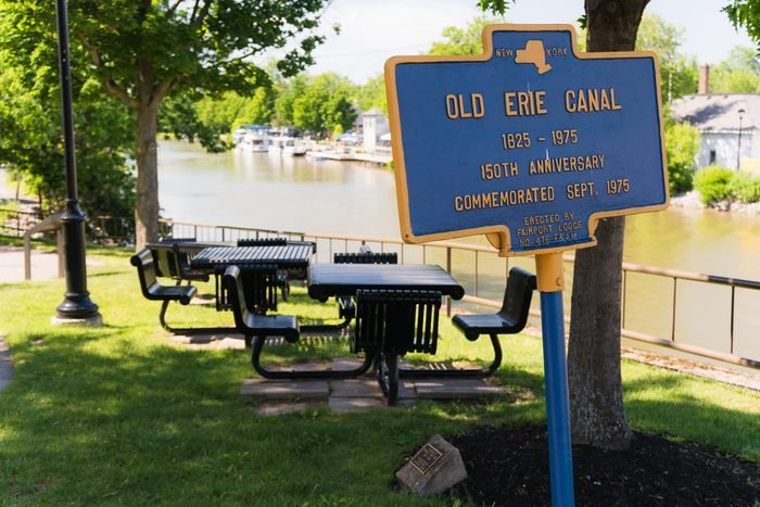 Historic sign and shady picnic tables alongside erie canal in Fairport, New York