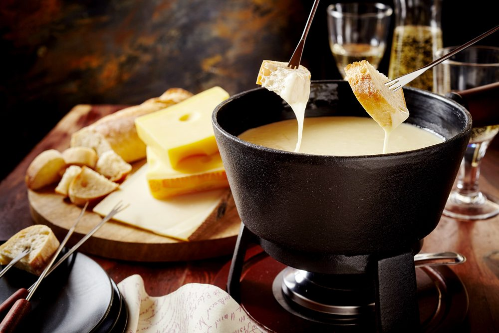 Dipping into a delicious cheese fondue made with a blend of assorted melted cheeses and wine or cider