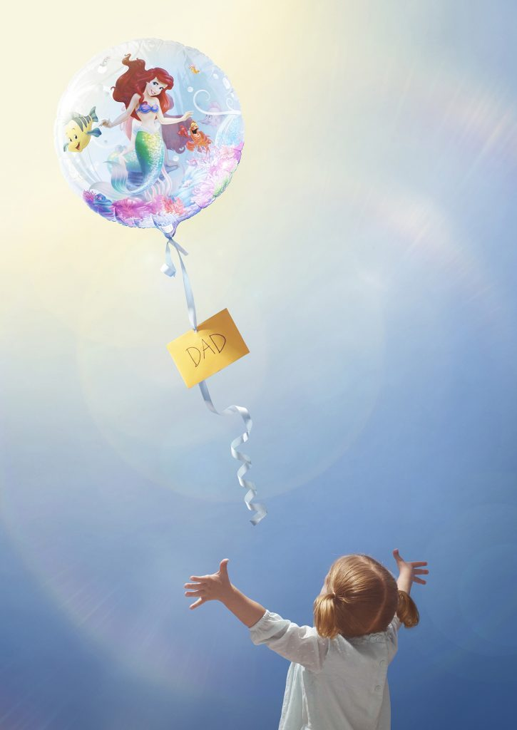 little girl reaching for balloon