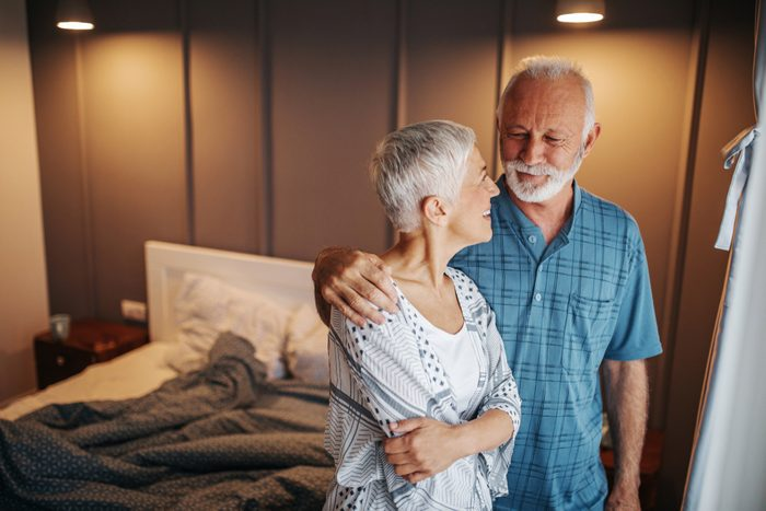 Senior couple hugging and smiling in the bedroom