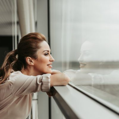Side view happy woman dreaming while looking at window indoor. She having rest during labor