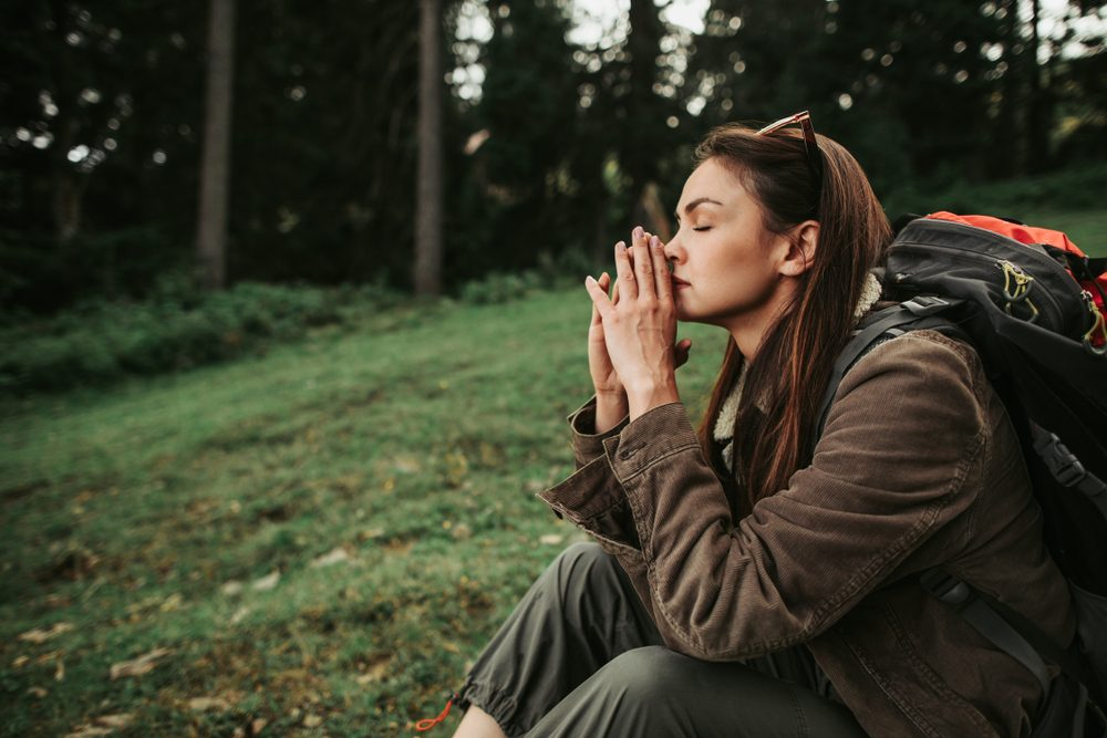 Healing power of nature. Side view portrait of beautiful girl with closed eyes resting in the forest. She is keeping hands near face and thinking about something important
