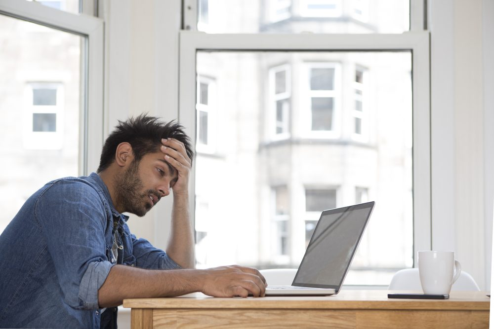 Stressed and frustrated Asian man sitting at his laptop.