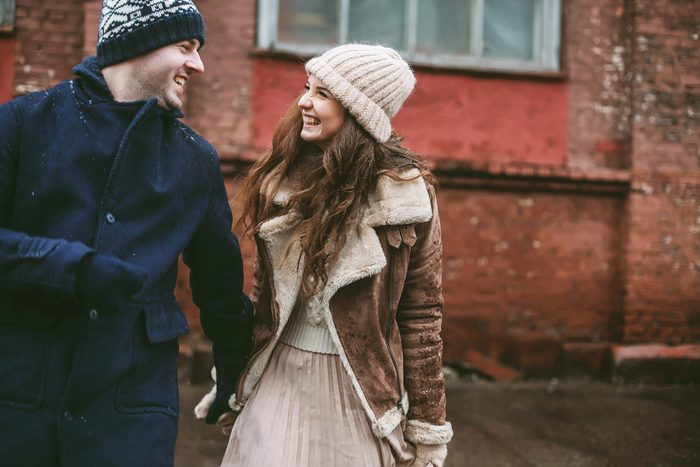 Young happy couple laughing and enjoying christmas spirit at the street with red bricks wall