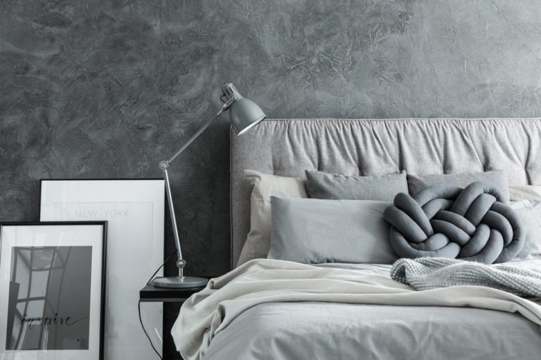 Close-up, side view of cozy modern bedroom with gray headboard