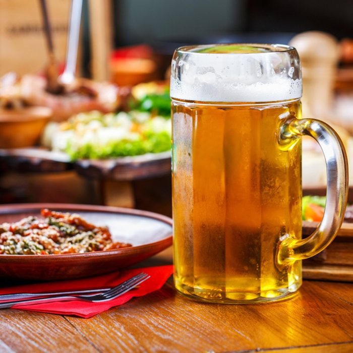 Cold, clear, light beer with foam in a faceted glass on the table with snacks in the pub