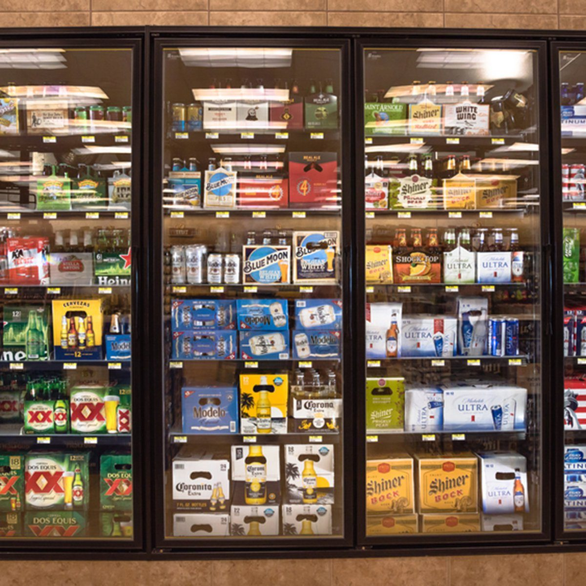Various bottles of craft, microbrew, IPA, domestic and imported beers from around the world on shelf display in supermarket cooler.