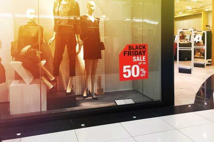 Window display with red sale board for Black Friday shopping. Vintage filter effect.