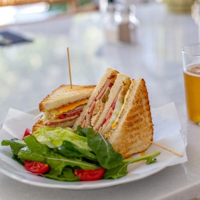Club Sandwich with a Glass of Beer on a Table. Fast food.