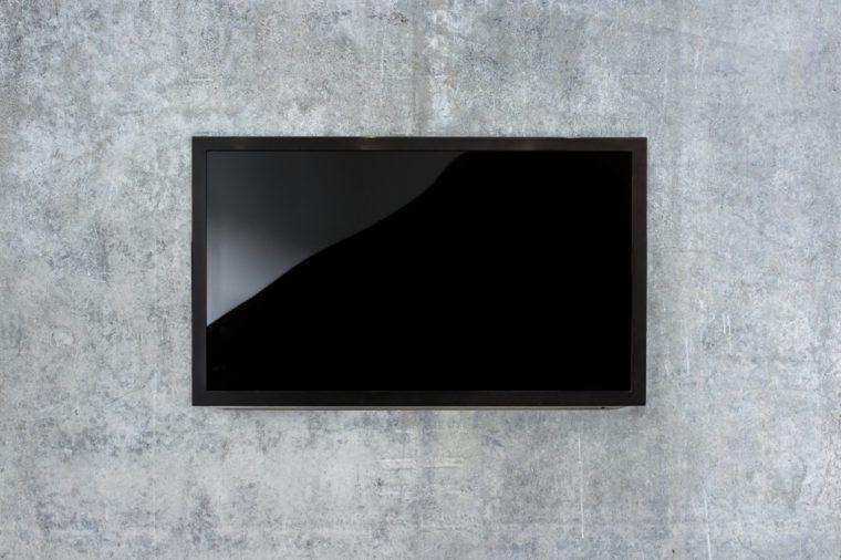 Black LED tv television mockup, blank on gray concrete background