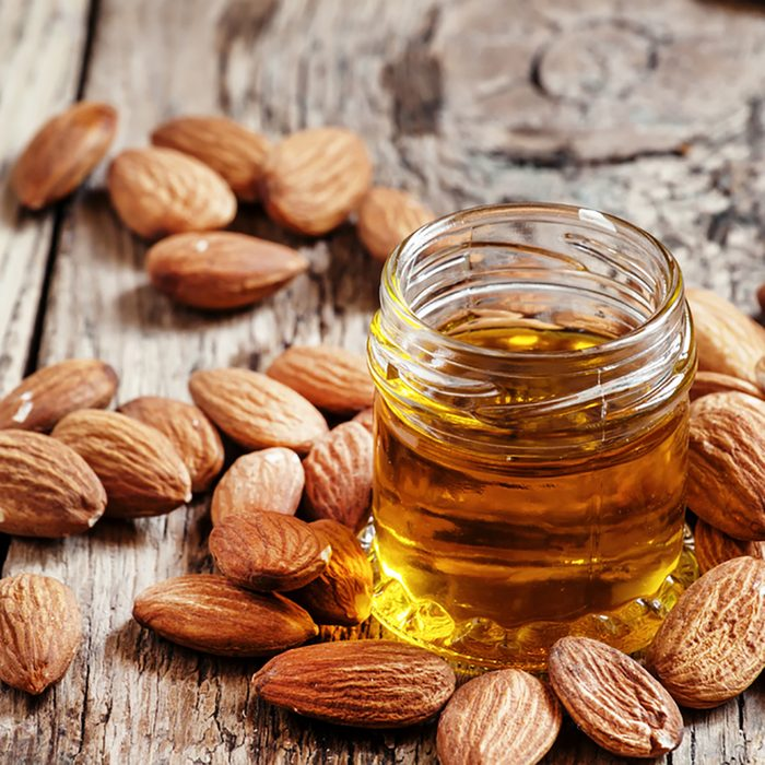 Sweet Almond Oil, first extraction, in a small glass jar, dry almond nuts on an old wooden background, selective focus; Shutterstock ID 386246191; Job (TFH, TOH, RD, BNB, CWM, CM): Taste of Home