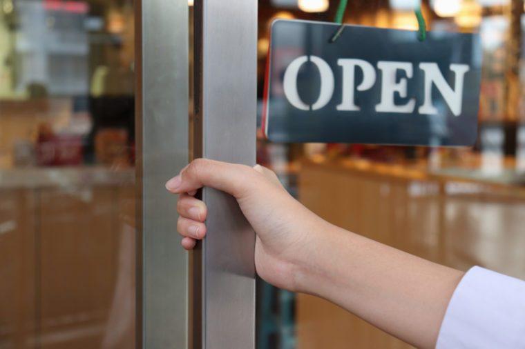 hand on handle door for open to entering restaurant