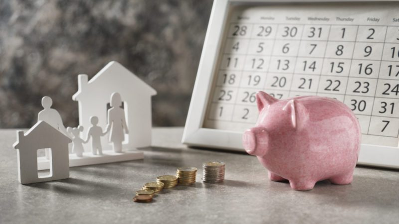 Composition with piggy bank, calendar and model of house and family on grey table. Concept of saving money for buying new house