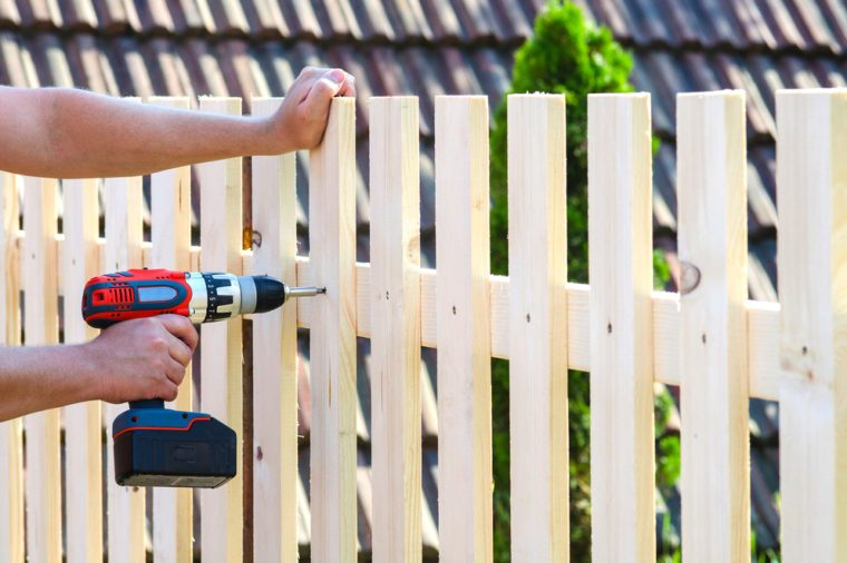 building a wooden fence with a drill and screw. Close up of his hand and the tool in a DIY concept.