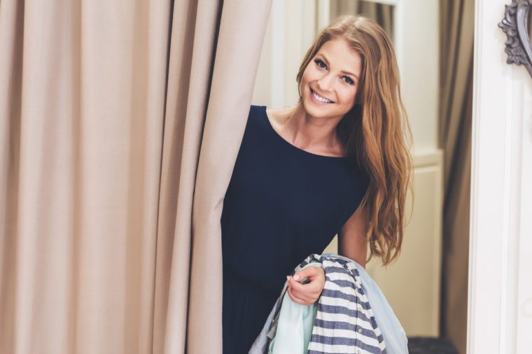 Can you bring me on more dress please! Beautiful young woman holding clothing and looking at camera with smile while standing in fitting room at the store