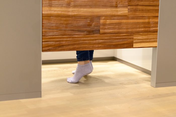 Woman standing on tip toe in a changing room at a store as she tries on clothes, view of her feet under the wooden door
