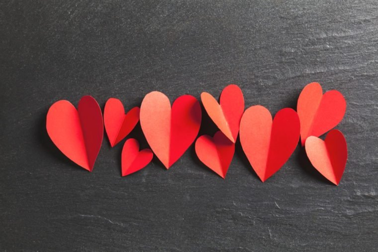 Red handmade paper hearts on a slate background