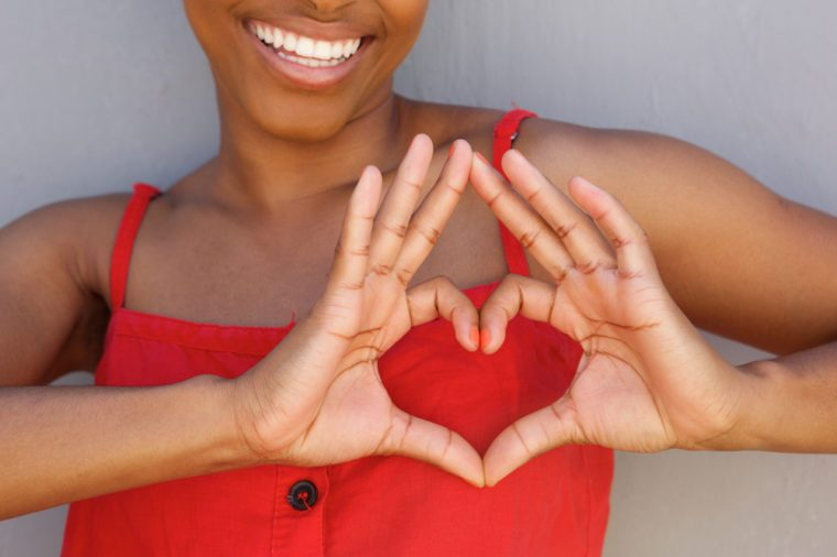 Close up portrait of young woman smiling with heart shape hand sign