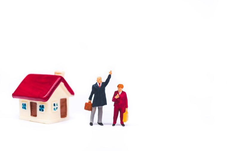 Miniature people, man and woman standing at mini house isolated on white background using as business and family concept