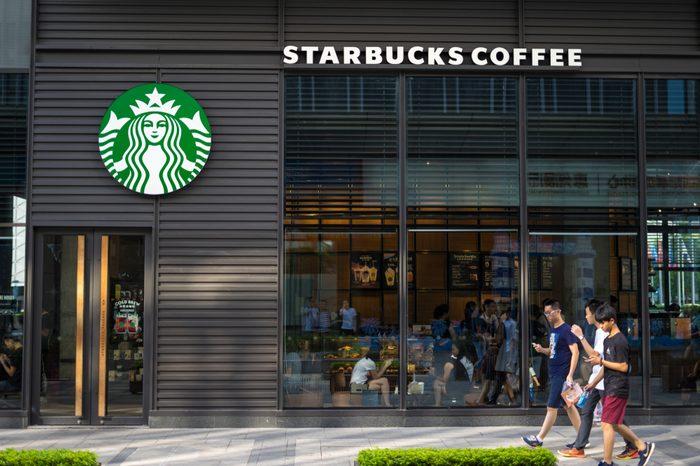 Huizhou, China - Aug. 2017: Some younger men walking outside the Starbucks Coffee store storefront in Huizhou urban