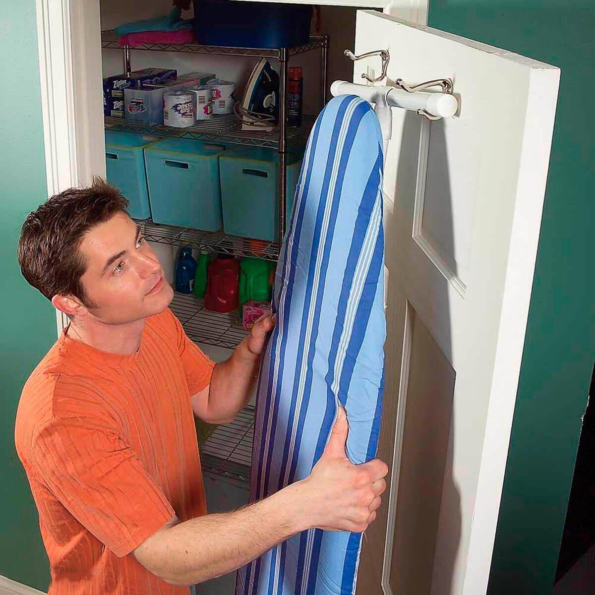 man hanging ironing board on hooks