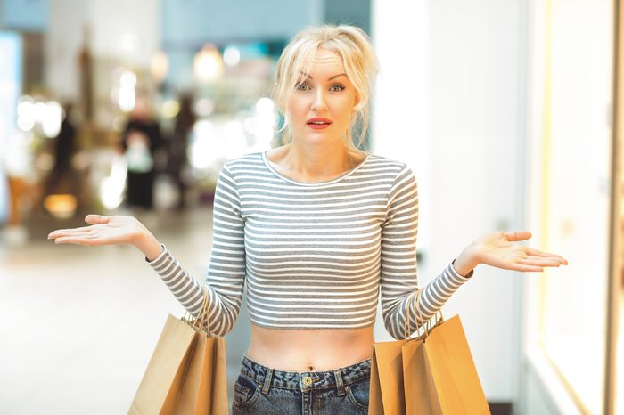 Spent all the money. Beautiful mature woman looking confused spreading her arms at the shopping mall after spending all her money broke poor no money helpless confused lost perplexed shopaholic