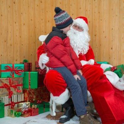 A boy visiting Santa in his grotto at Christmas.