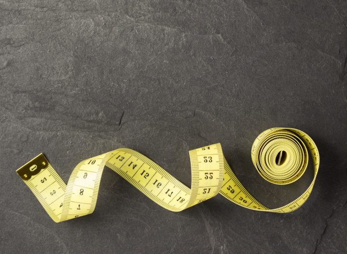 tape measure on slate stone background, top view