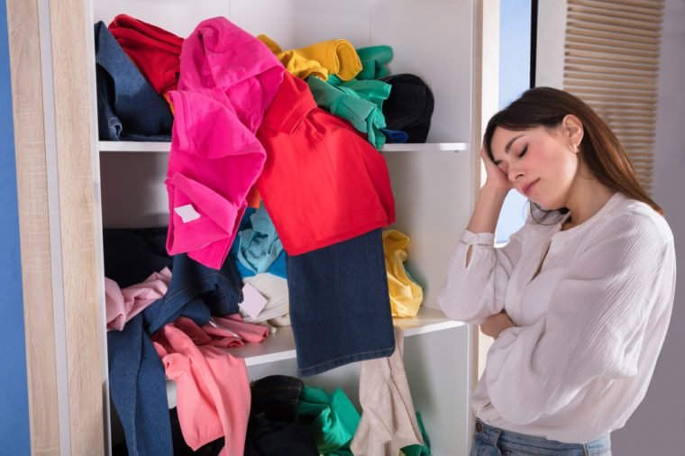 Side View Of A Young Woman Sleeping Near Messy Clothes On Shelf