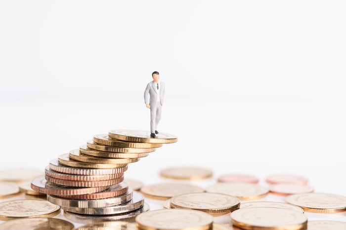 Miniature successful business people stand on top of golden money coins isolated on white background,high risk high return concept