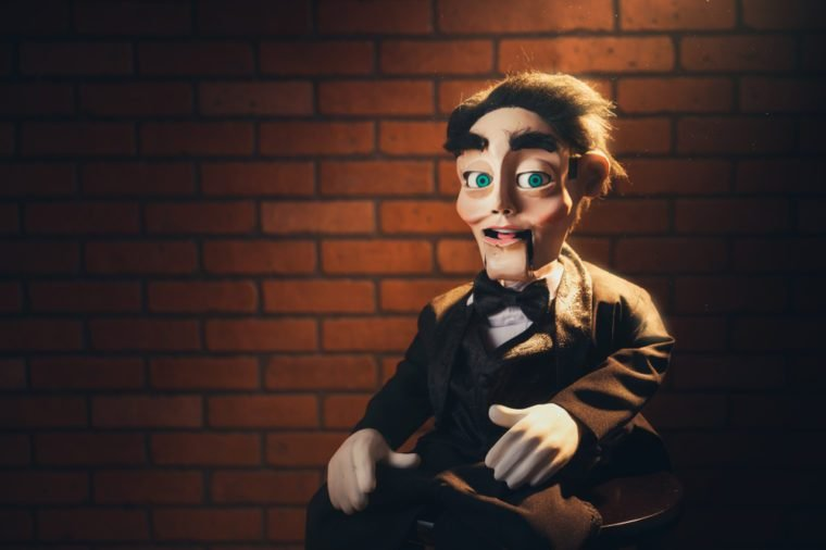 Creepy ventriloquist dummy with green eyes sitting on a wooden stool,