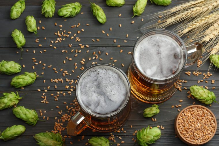 Glass beer with hop cones and wheat ears on dark wooden background. Beer brewery concept. Beer background. Top View