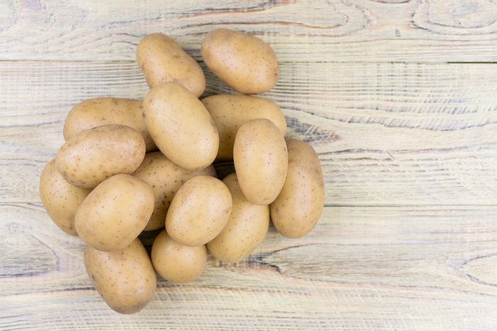 Potato tubers on a wooden background.