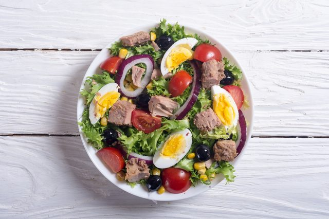 Tuna salad with tomatoes , olives , eggs and onion .