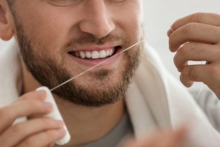 Young man flossing teeth, closeup